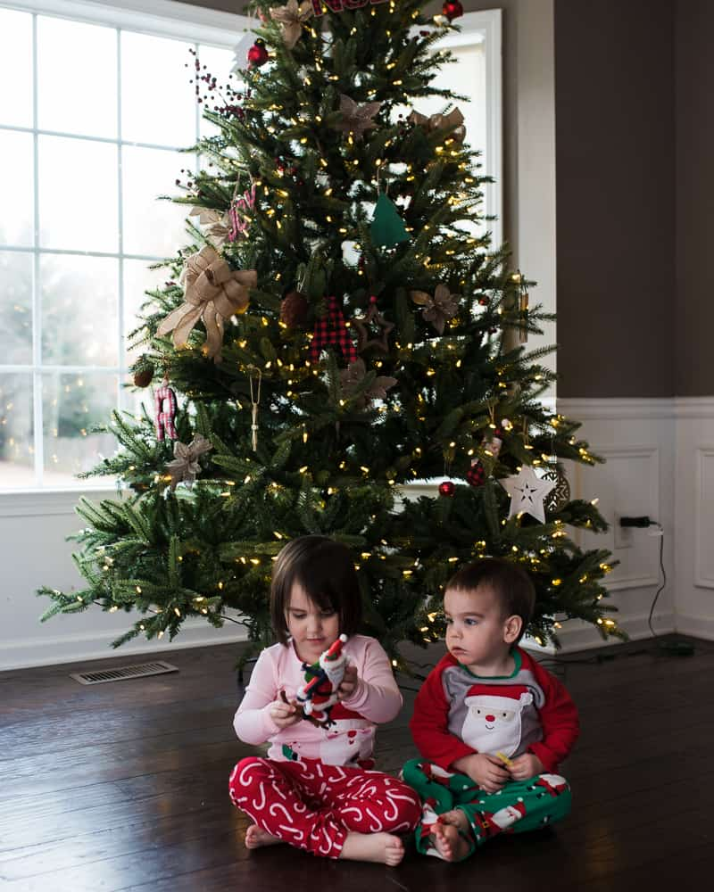 toddlers sitting in front of Treetopia Christmas tree with farmhouse decor