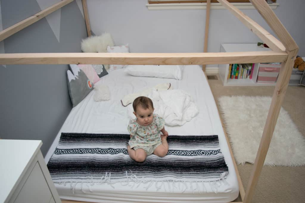 Toddler sitting on Montessori style floor bed with wooden house frame in new baby nursery makeover