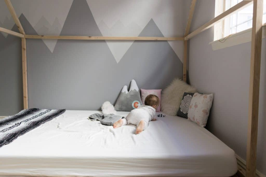 Montessori style floor bed with wooden house frame against DIY mountain wall mural