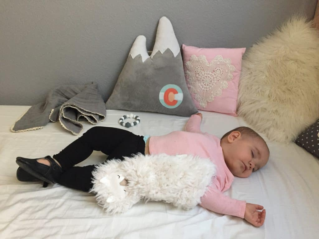 Baby girl sleeping with mountain pillow in her new DIY mountain themed nursery