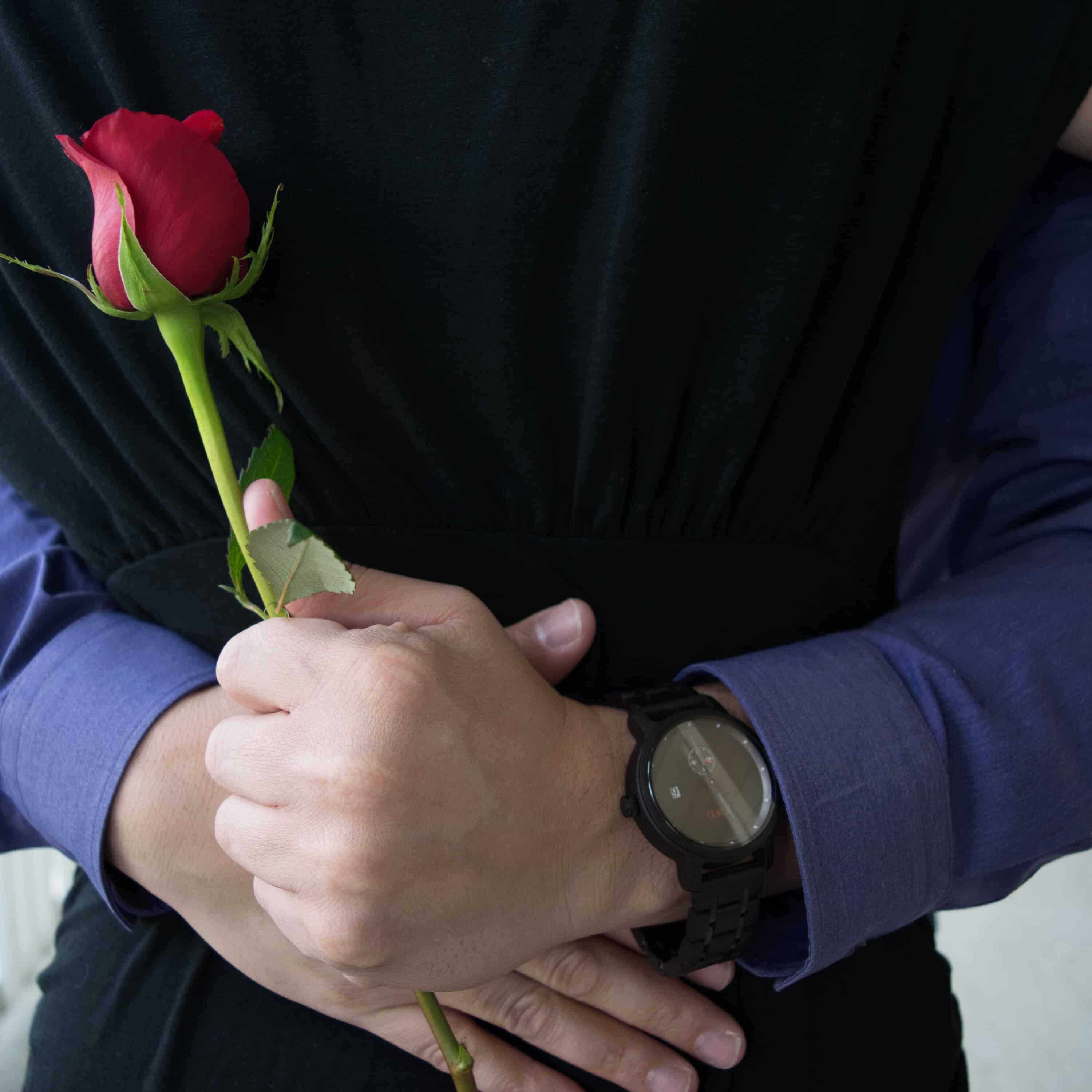 Man holding rose while hugging wife - Valentine's Day Gift for Him