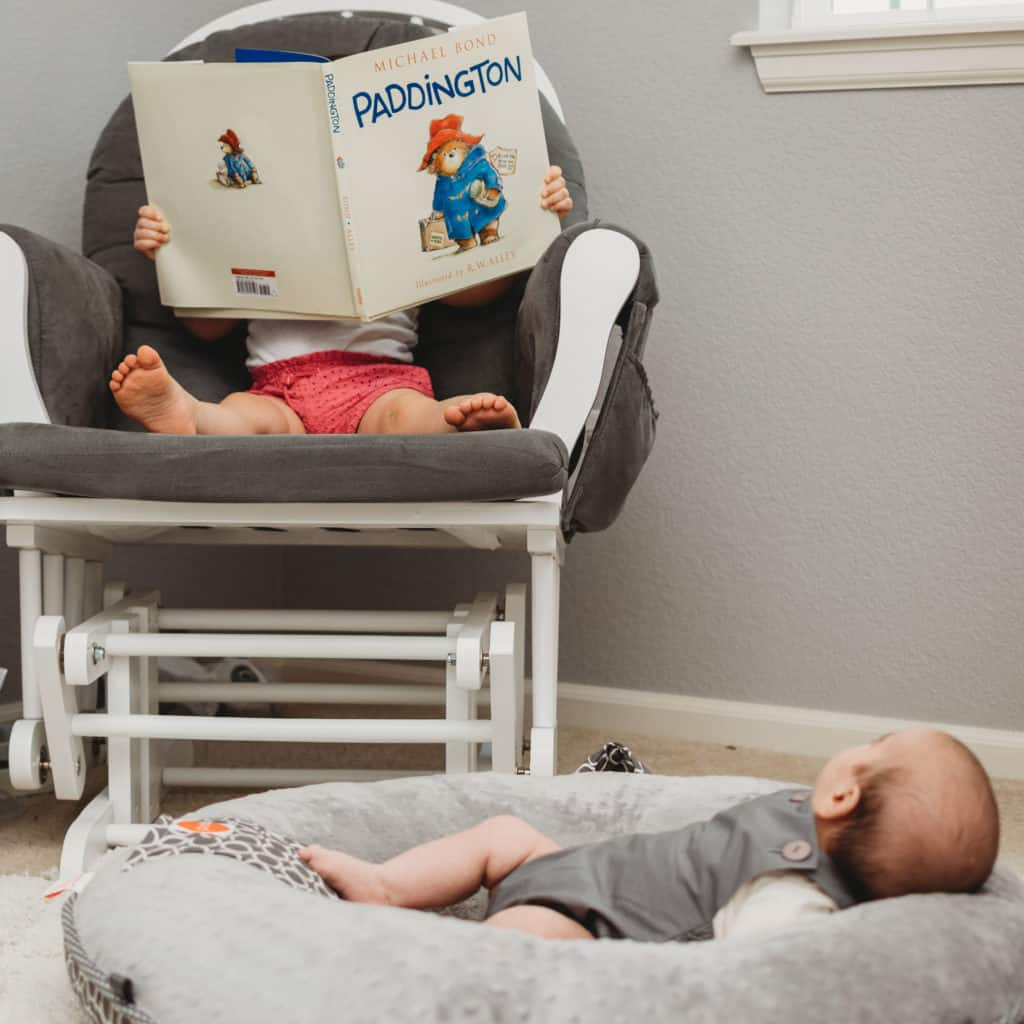 Toddler can encourage reading by reading book to baby brother