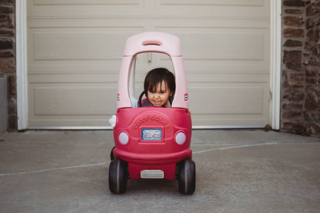 Toddler girl in cozy coupe car