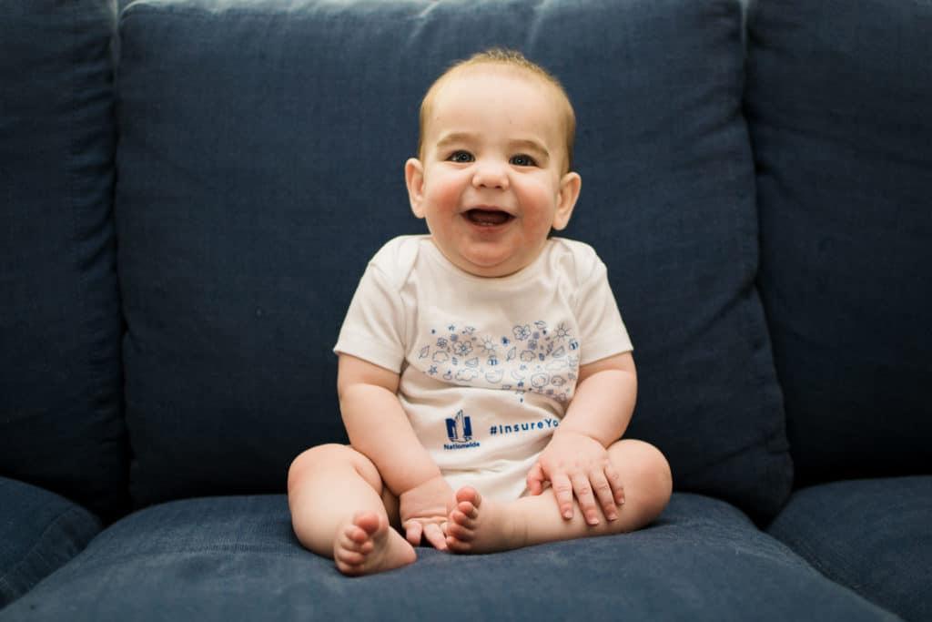 baby boy wearing Nationwide insurance onesie