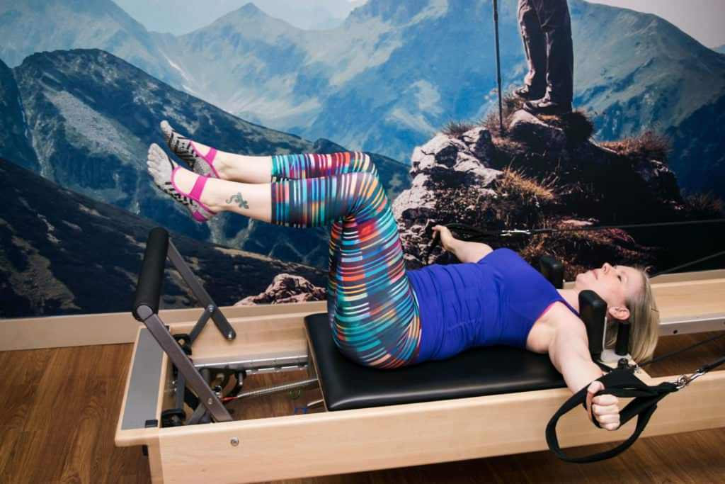 Momblogger Amanda Seghetti using reformer at Club Pilates - read her complete postpartum workout review!