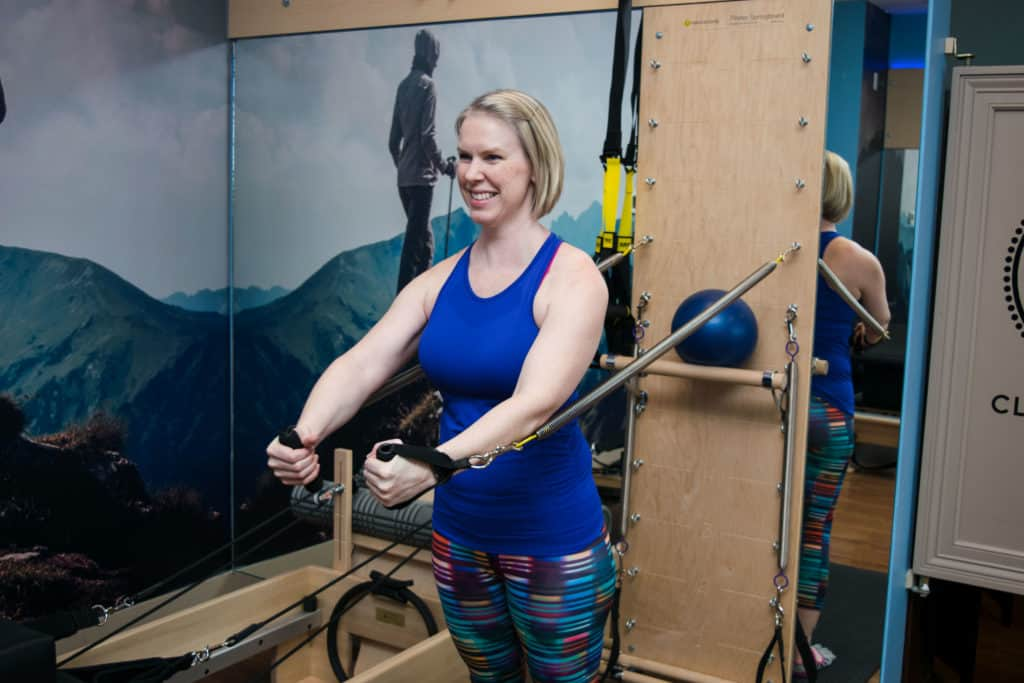 Momblogger Amanda Seghetti exercising her arms with springboard at Club Pilates.