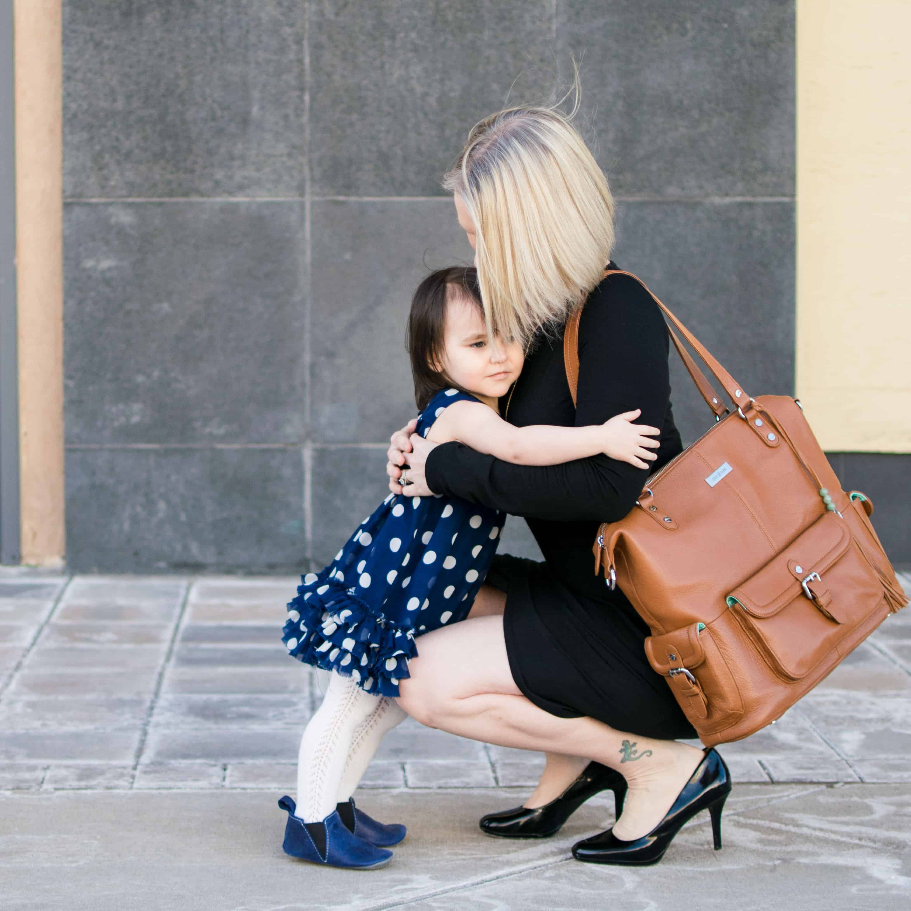 Momblogger Amanda Seghetti hugging 2 year old while carrying Lily Jade diaper bag