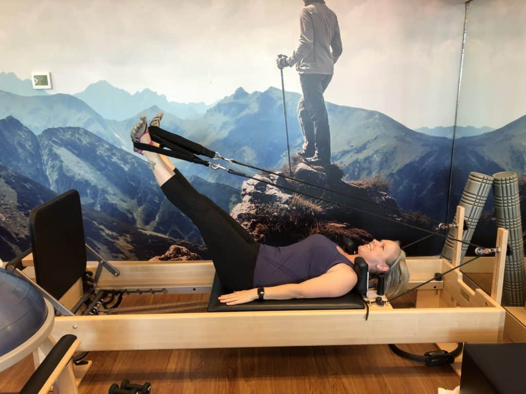 Momblogger Amanda Seghetti working her core on the pilates reformer at Club Pilates in Greenwood Village, Colorado