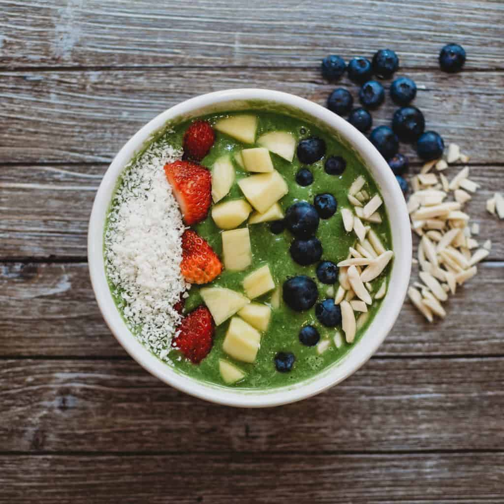 Colorful smoothie bowl with coconut strawberries mango blueberries and almonds on wooden background | Cancer Prevention Tips