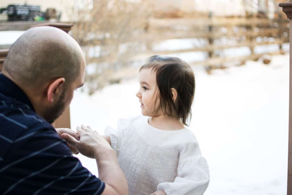 Dad rubbing sunscreen on toddler on snowy day | Amanda Seghetti