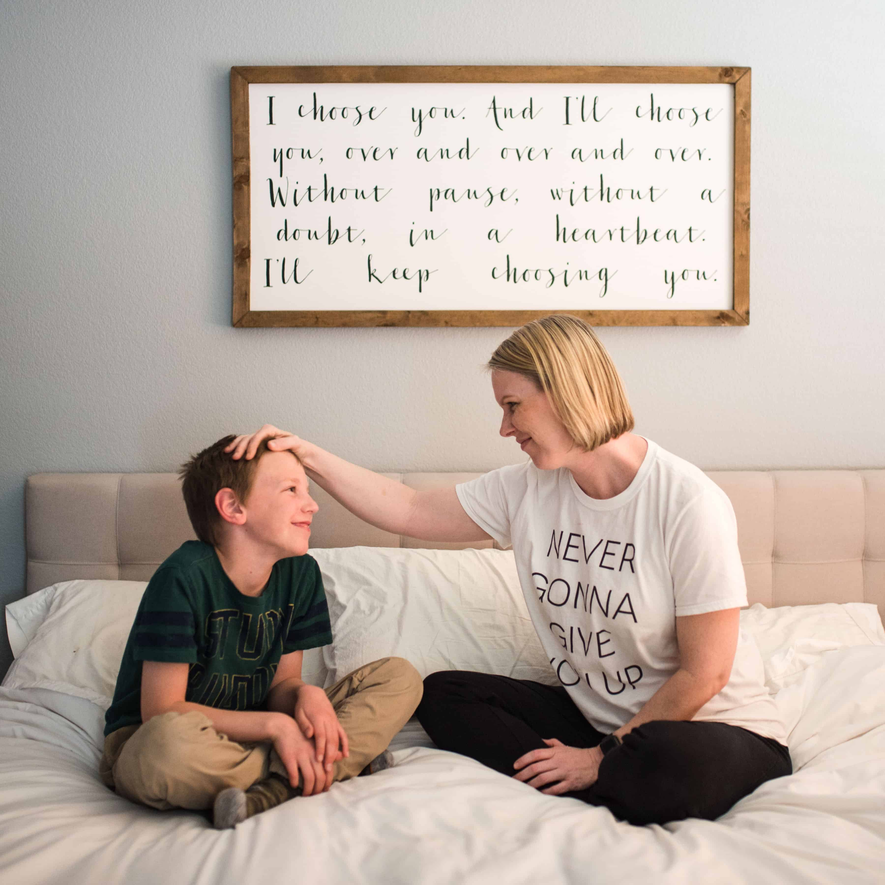 Mom and son sitting on bed talking about vaping
