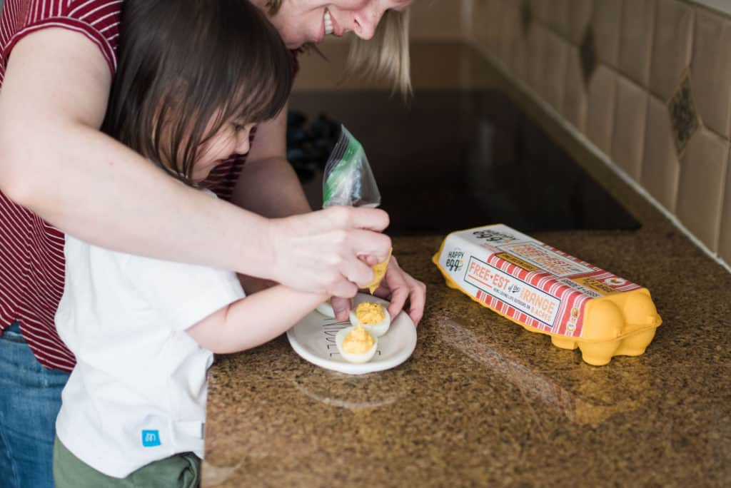 mom and toddler making deviled eggs - activities for bored kids