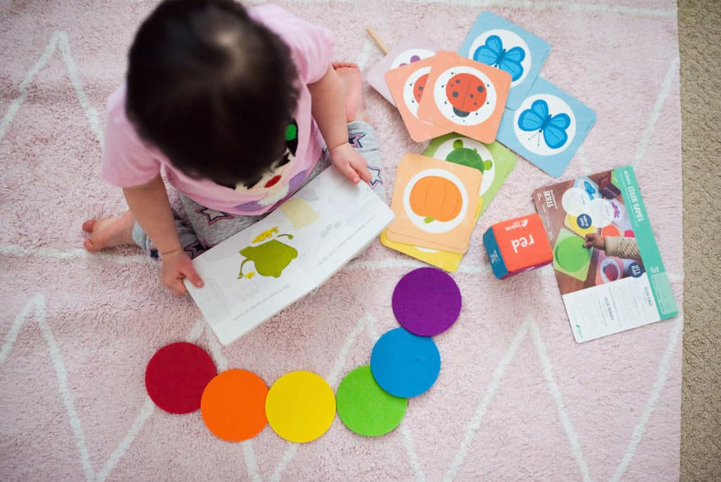 Toddler playing with KiwiCo Tadpole Crate color matching activity