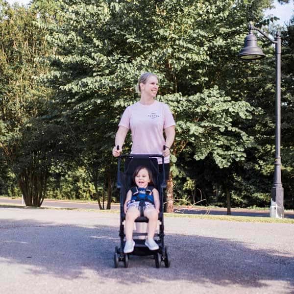 Lifestyle blogger Amanda Seghetti pushes toddler in lightweight travel stroller outside.