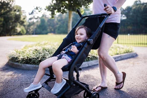 Toddler Aren Seghettirides in lightweight travel stroller by Delta Children