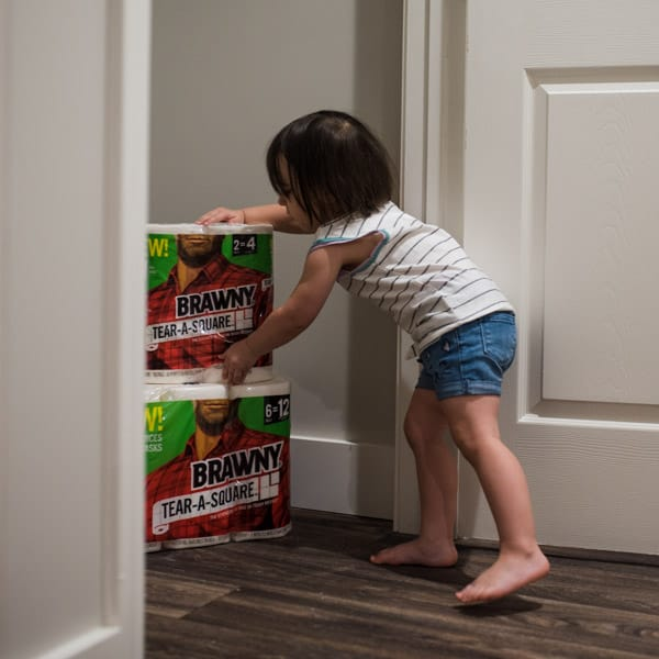 Toddler reaching for stockpile of Brawny Tear a Square paper towels