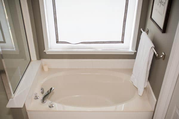 White curtain in master bathroom next to large bathtub