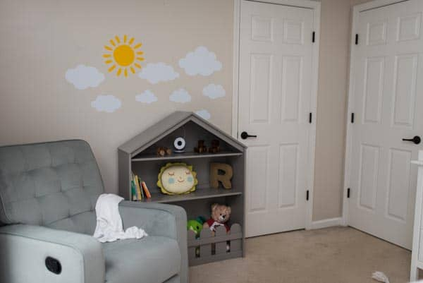 Gray glider recliner and gray happy home bookcase in gender neutral nursery