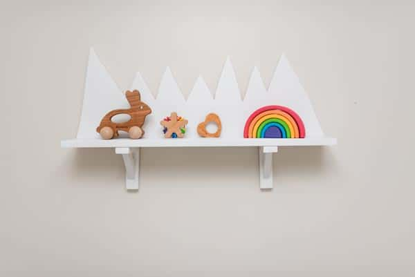 White wooden mountain shelf with baby nursery decor