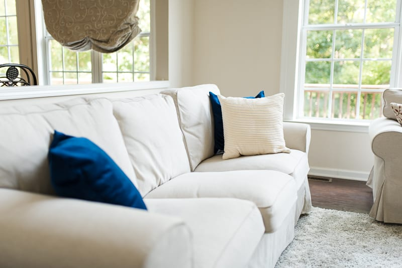 neutral couch with blue and ivory textured pillow covers