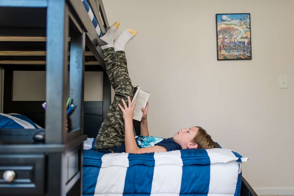 boy reading on bunk beds with tween boys bedroom decor