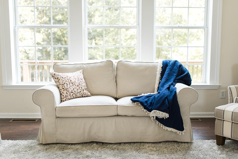 neutral ikea couch with cozy blanket for fall
