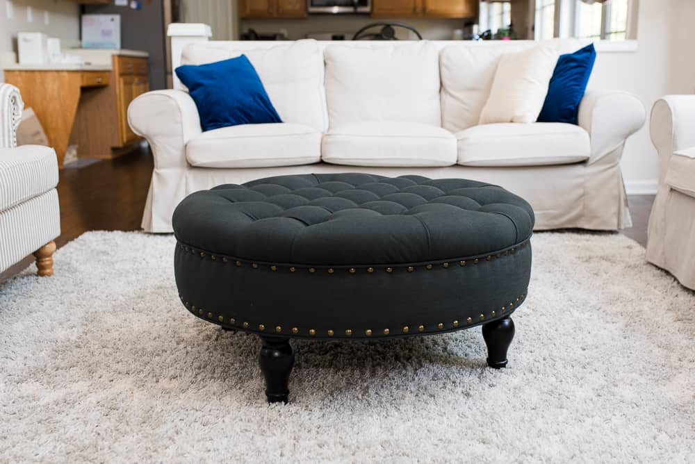 Lifestyle blogger Amanda Seghetti uses a dark colored tufted cocktail ottoman to add a pop of color to her neutral living room.