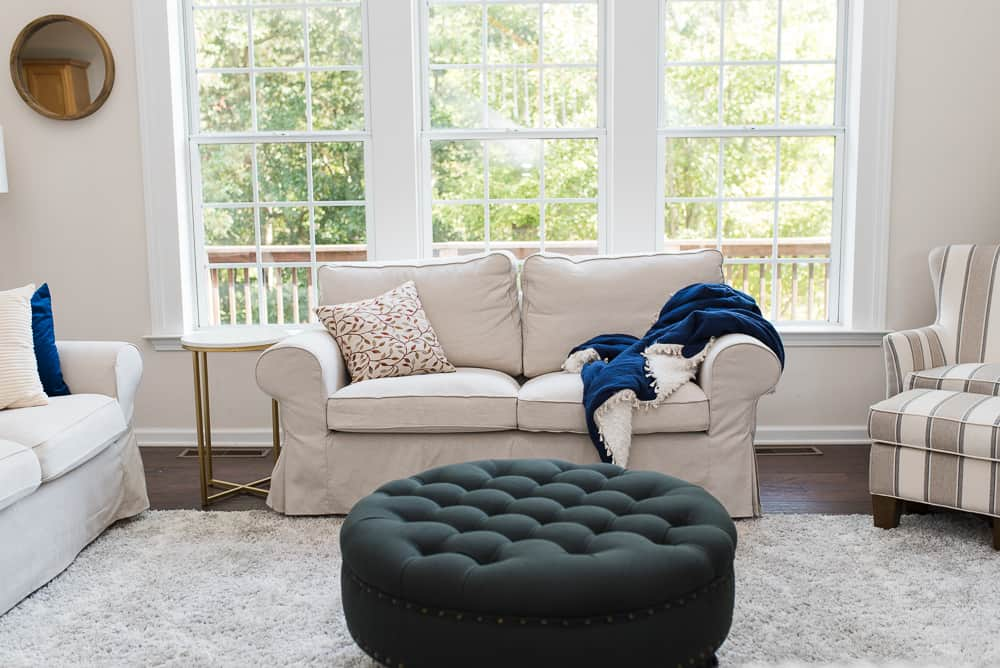beige loveseat and tufted ottoman