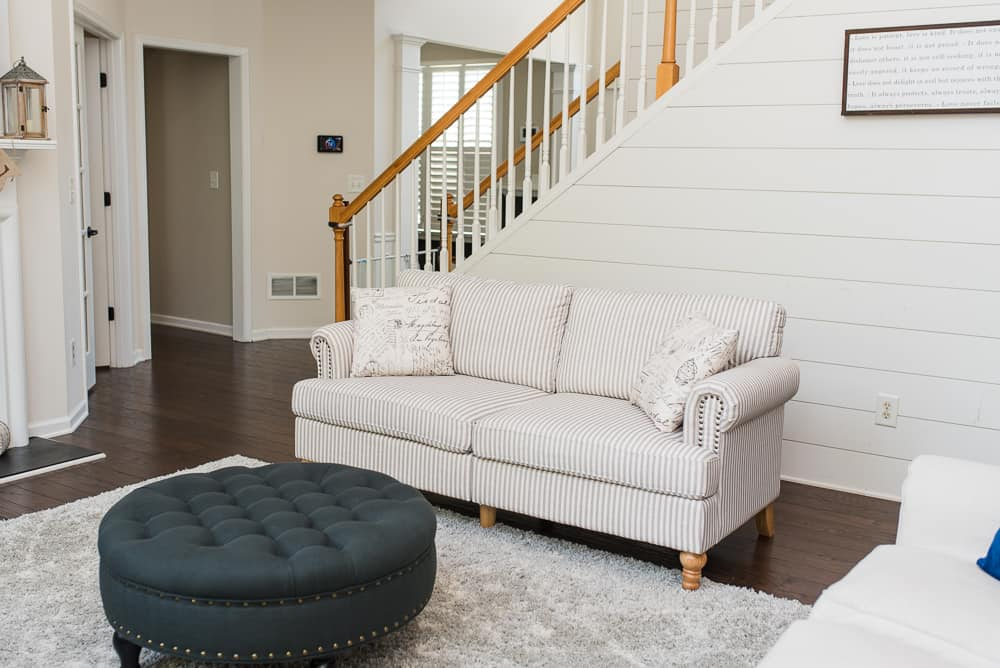 neutral living room accent sofa and dark tufted ottoman