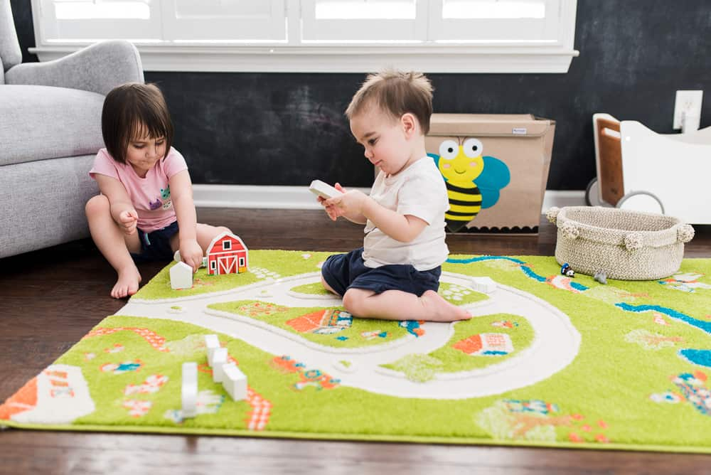 toddler boy and girl playing with farm rug