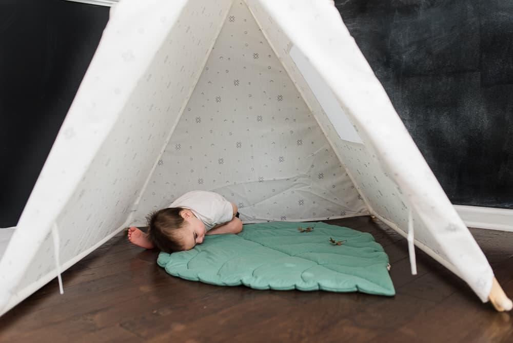 toddler boy on leaf mat inside tent