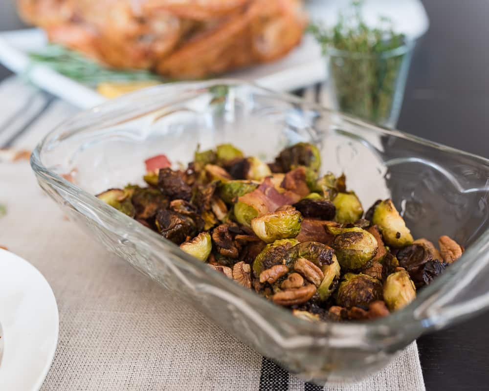 Glass dish of roasted Brussels sprouts with pecans