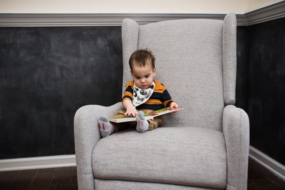 Toddler reading book in comfy rocking chair