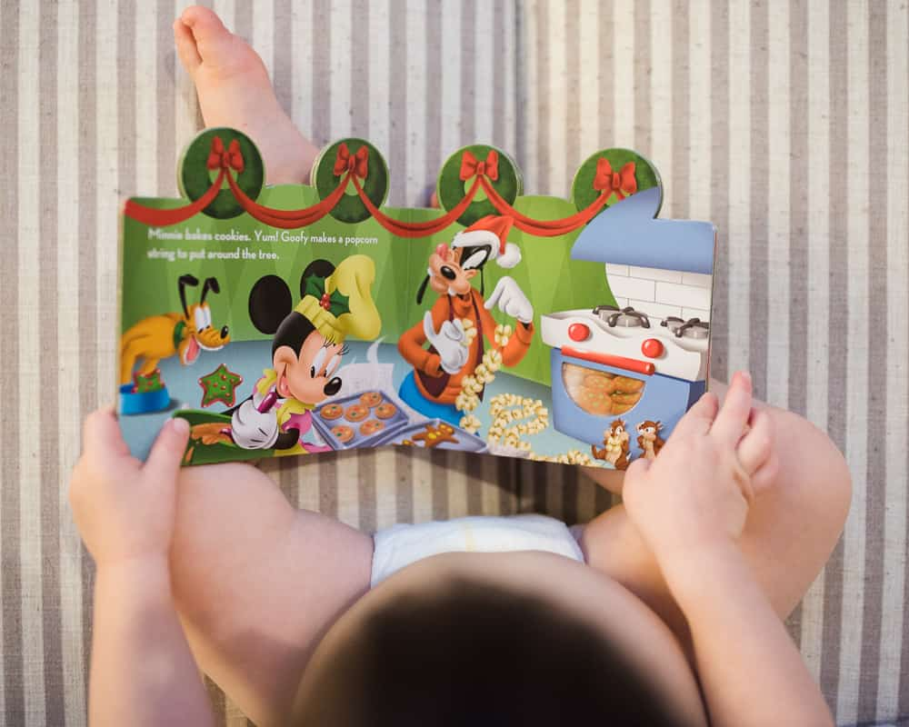 Toddler reading Mickey Mouse Clubhouse Christmas board book