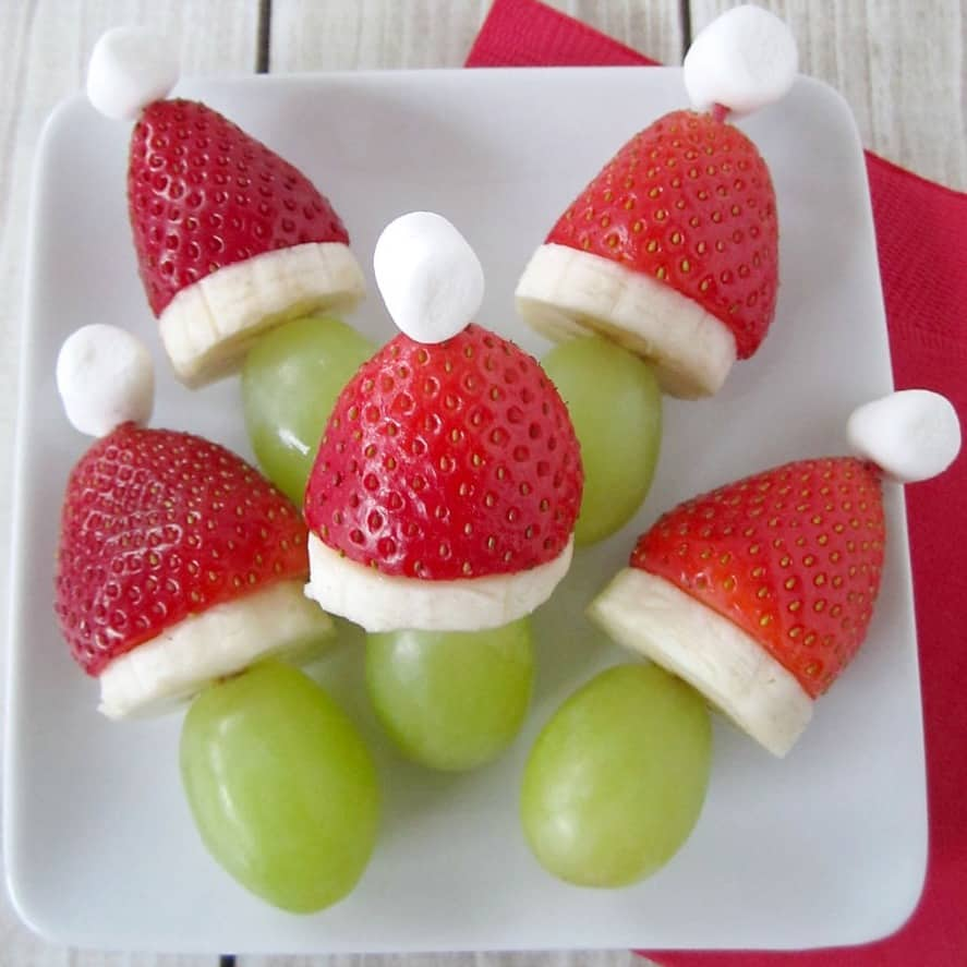 Grinch fruit kabobs with strawberries, bananas, and grapes.
