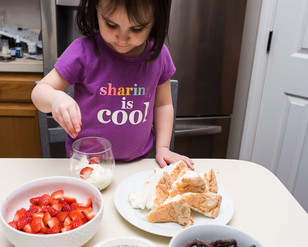 toddler preparing healthy fruit dessert