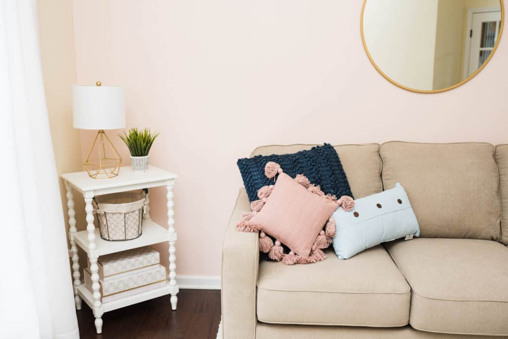 Greige guest room sofa sleeper and white end table with pink, blue, and gold accents