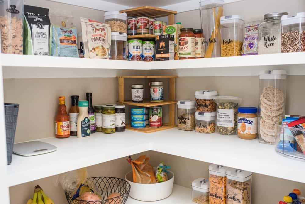 Bamboo shelves and containers are helpful for pantry organization.
