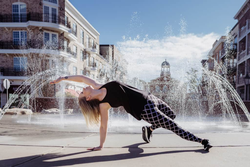 Healthy parenting blogger Amanda Seghetti demonstrates yoga pose wild thing in front of fountain in downtown Alpharetta Georgia