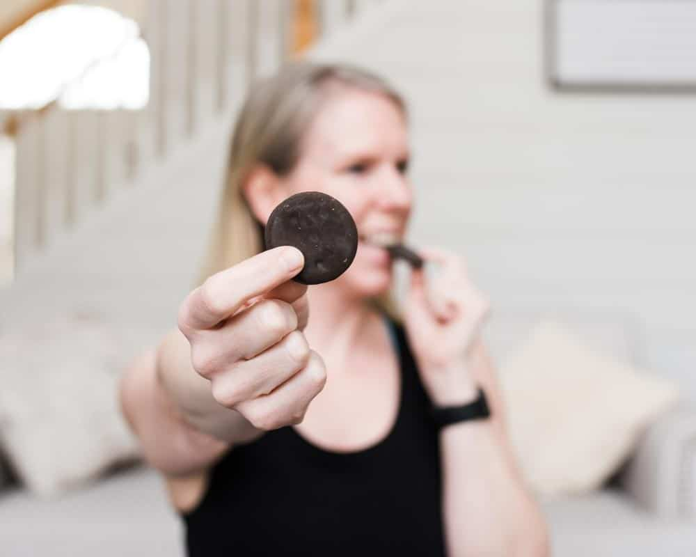 healthy lifestyle blogger Amanda Seghetti demonstrates how to stop food guilt as she bites into a Girl Scout Thin Mint Cookie