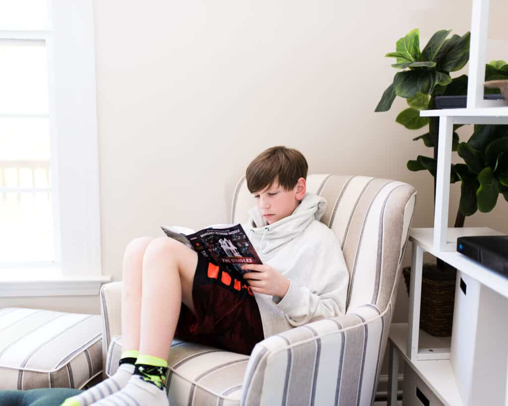 teen shelter-at-home reading in chair