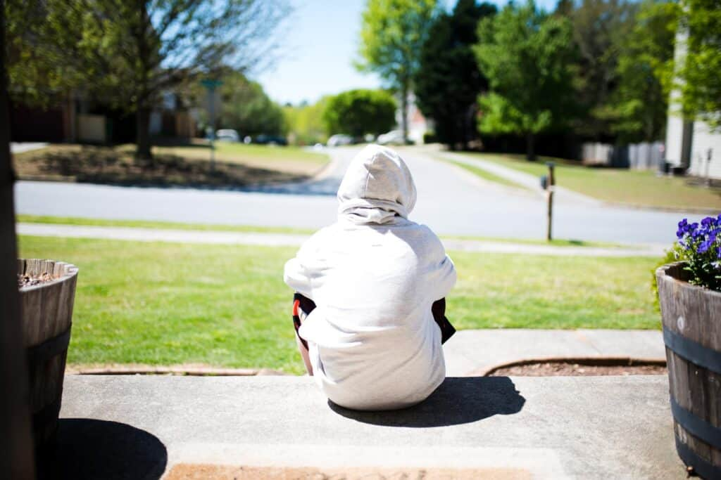 teen sitting on front porch wearing hoodie while social distancing
