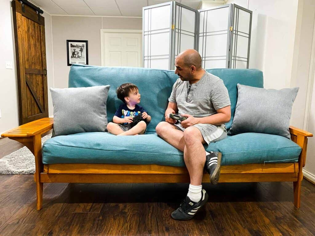 dad and son on futon playing video games
