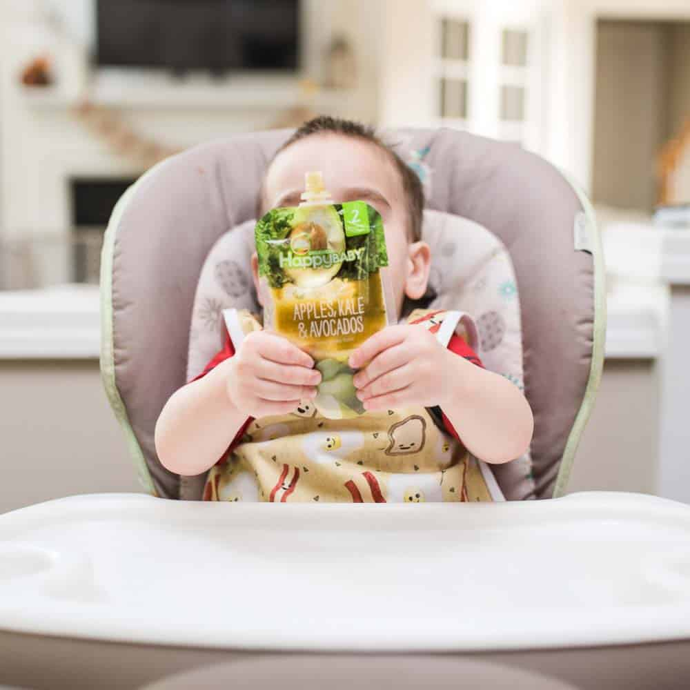 baby in high chair holding food pouch