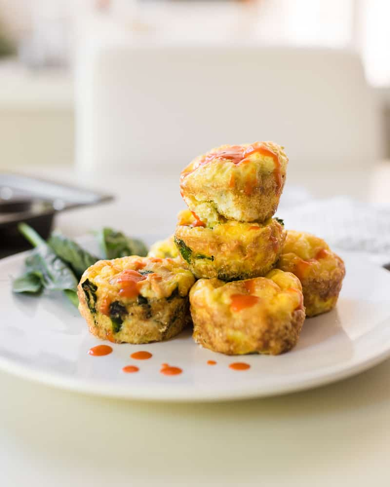 buffalo sauce on stack of egg muffins vertical - Amanda Seghetti