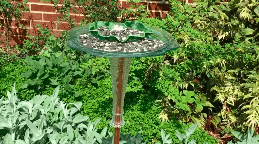 A DIY bird feeder made from recycled glass dishes and a vase.