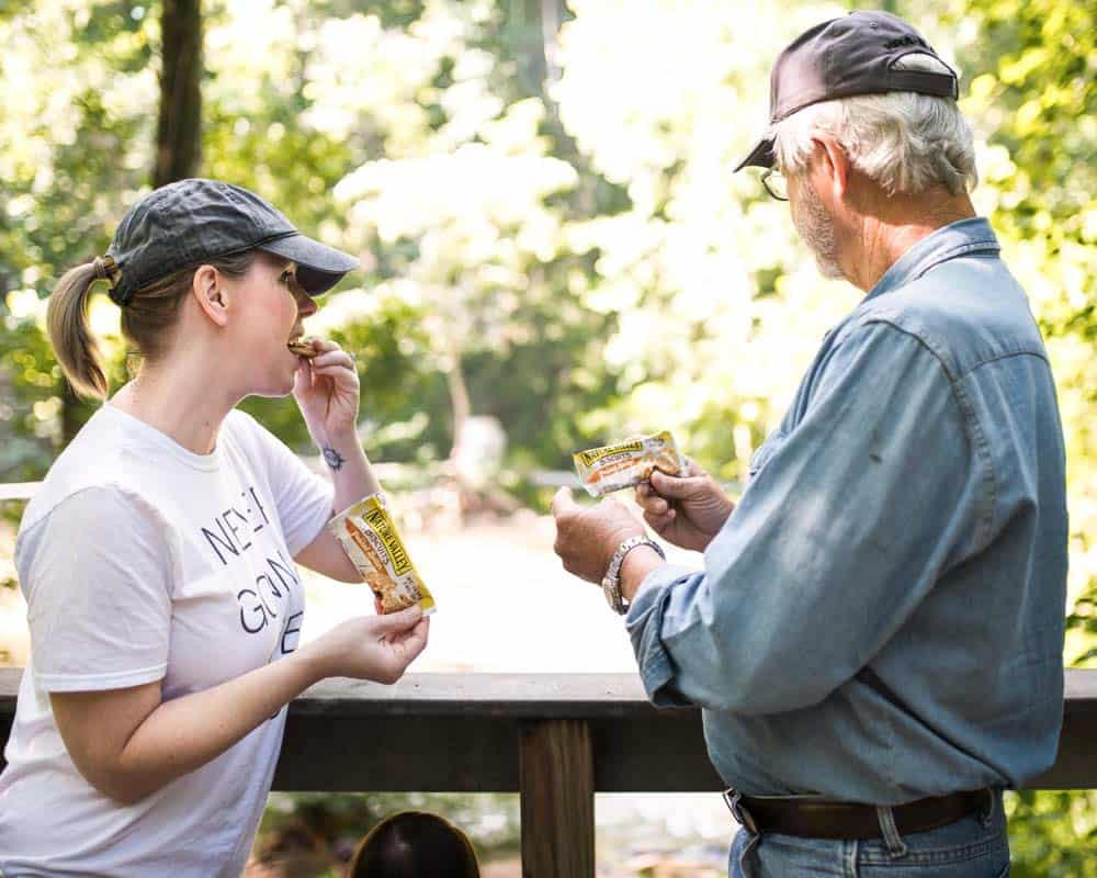 woman and man eating convenient snacks with flexible packaging in nature