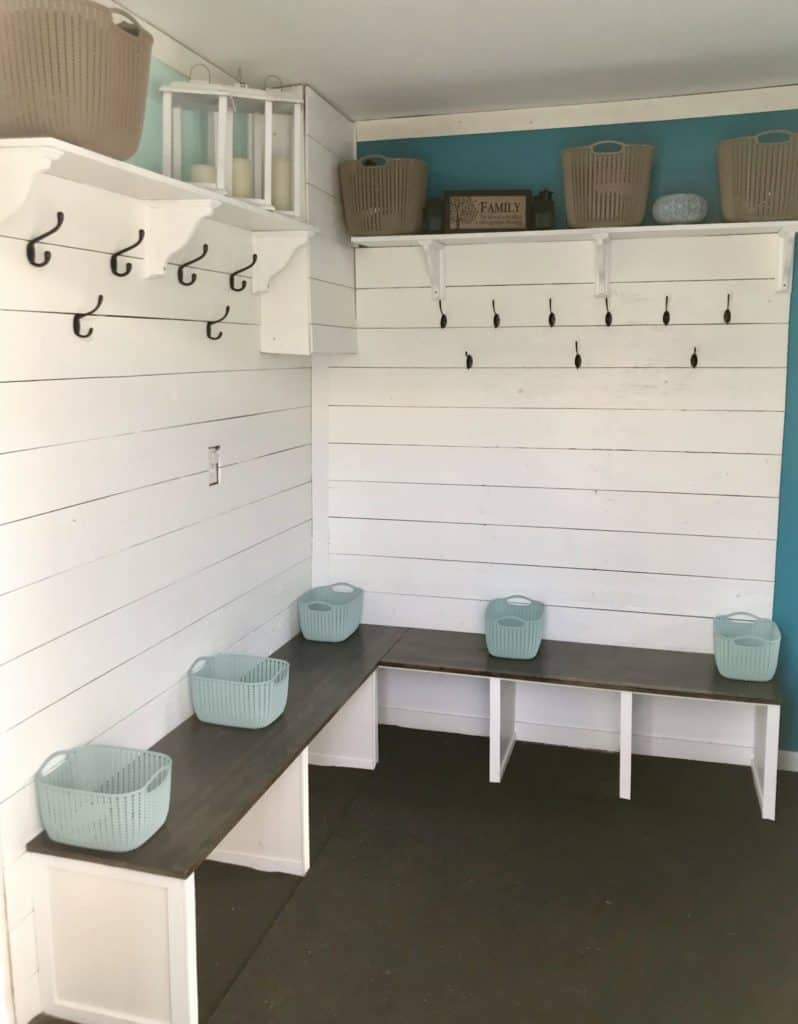 finished mudroom entryway with shiplap walls and bench with decor