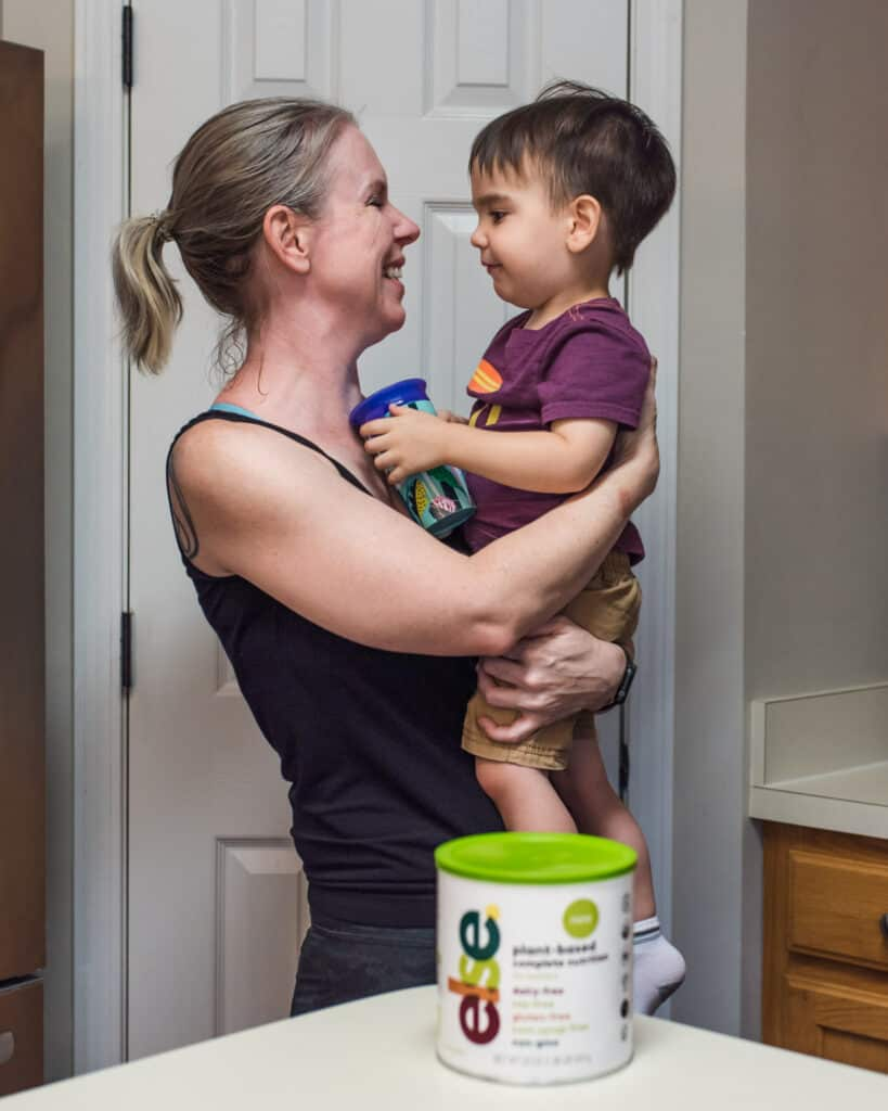 mom holding toddler next to can of else nutrition plant based toddler formula