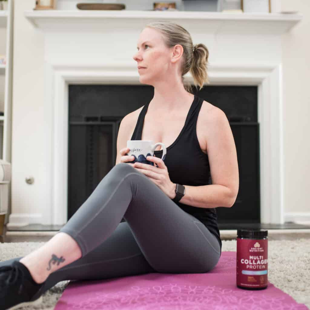 sitting on yoga mat with coffee and ancient nutrition collagen